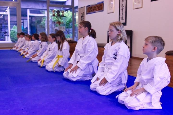 Kinder sitzen in Meditationshaltung
